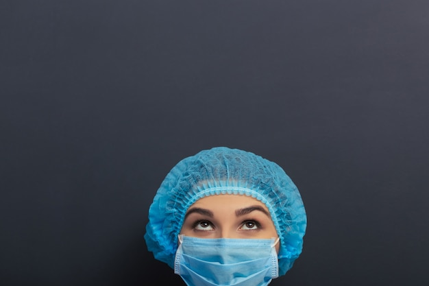 Beautiful doctor in white medical gown, cap and mask.
