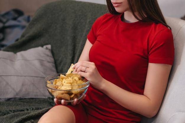 아름 다운 국내 여자 칩을 먹고, tv를보고, 소파에 앉아.