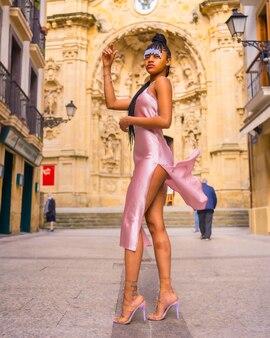 Красивая доминиканская этническая девушка с косами в красивом розовом платье. мода наслаждаясь летом в красивой городской церкви, вертикальное фото