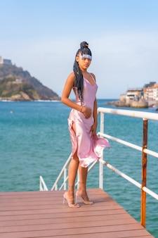 Красивая доминиканская этническая девушка с косами в красивом розовом платье. мода, наслаждающаяся летом на деревянной дорожке у моря