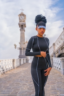 Beautiful dominican ethnic girl with with braids with full body suit. fashion posã© next to a beautiful beach clock