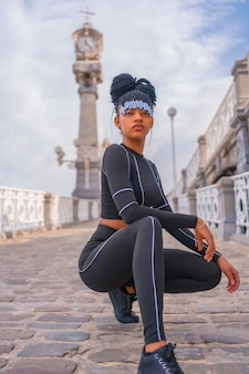 Beautiful dominican ethnic girl with with braids with full body suit. fashion posã© druzed next to a beautiful beach clock