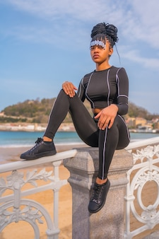 Beautiful dominican ethnic girl with with braids with full body suit. fashion, sitting on the beach railing in summer