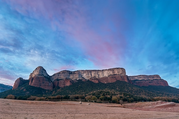 A beautiful dramatic blue-magenta sky above a multicolored mountain & forest in catalunya, spain