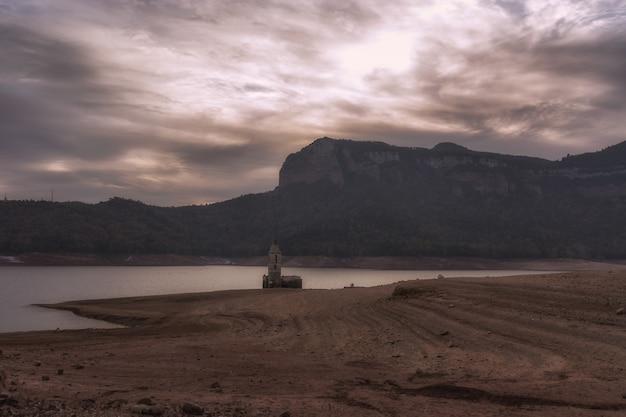 A beautiful but dramatic sepia, pale landscape of a smalla abandoned church beside a river at vilanova de sau, spain