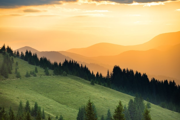 Beautiful dramatic sunset in the mountains. landscape with sun shining through orange clouds