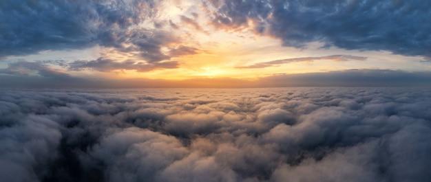 Красивое драматическое закатное небо над пушистыми облаками рано утром. вид с дрона.
