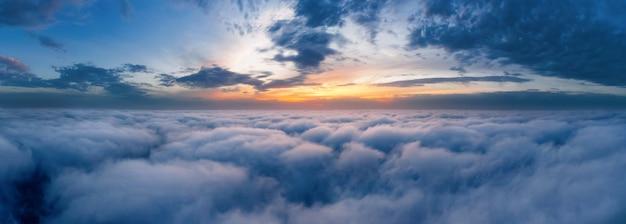 공중 무인 항공기보기에서 이른 아침에 솜털 구름 위의 아름다운 극적인 일몰 하늘.