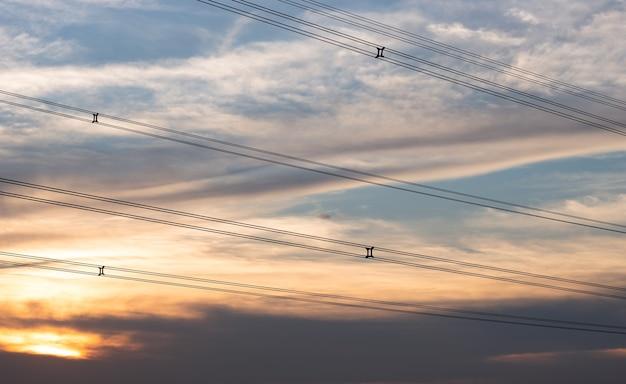 저녁에 고압선 위의 아름다운 극적인 일몰 하늘