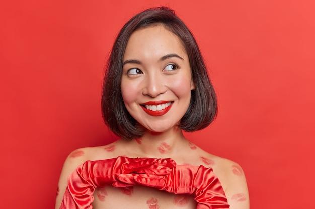 아름다운 꿈꾸는 아시아 여성은 장갑을 끼고 손을 잡고 부드럽게 시선을 돌리며 초대를 수락하고 밝은 빨간색 벽에 대고 데이트 포즈를 할지 결정합니다.