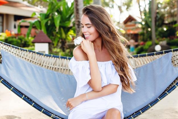 Красивая мечтательная девушка сидит в гамаке на пляже с закрытыми глазами, широко улыбаясь