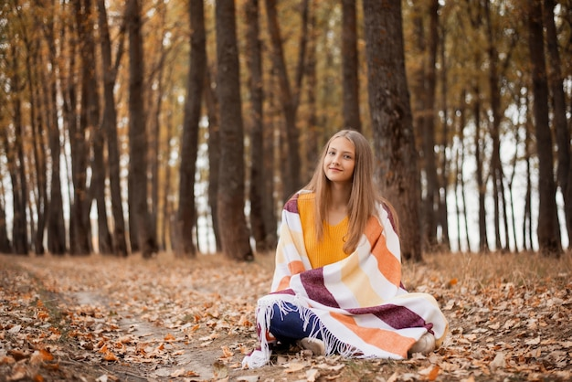 金色と黄色でいっぱいの公園に座って何かを考えている美しい夢のような女の子