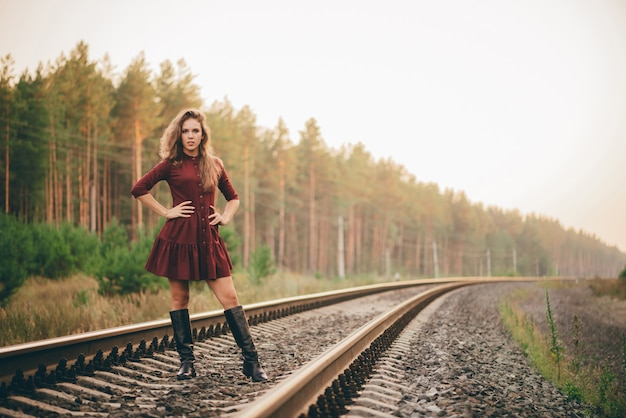 Beautiful dreamy girl with curly natural hair enjoy nature in forest on railway.