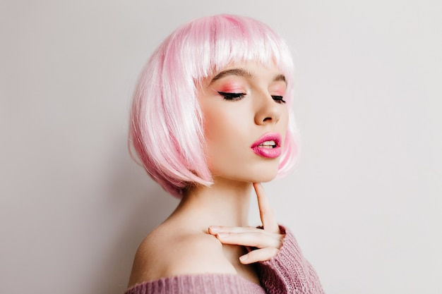 Beautiful dreamy woman wears pink peruke posing with eyes closed. indoor photo of charming  female model with bright makeup in periwig standing on light wall.