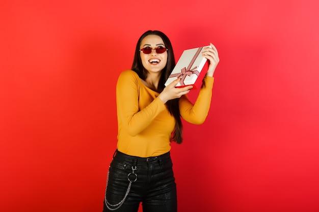 Красивая мечтательная молодая женщина держит подарочную коробку и встряхивает коробку, изолированную на красном фоне