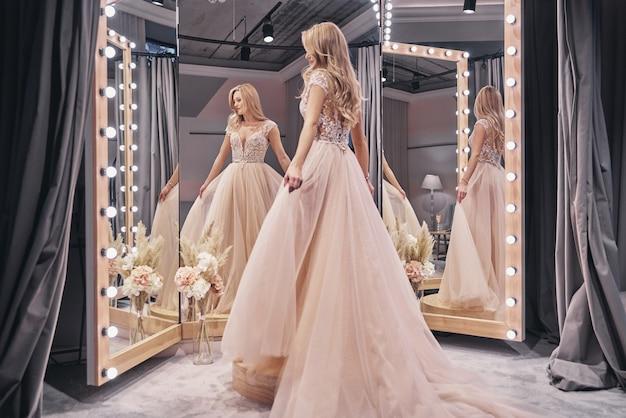 아름다운 드레스. 신부 가게에서 거울 앞에 서있는 동안 웨딩 드레스를 입고 매력적인 젊은 여자의 전체 길이