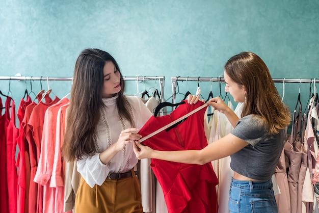 美しい洋裁は、クライアントのためにファッションストアでモダンなドレスを測定します。セールコンセプト、ブラックフライデー