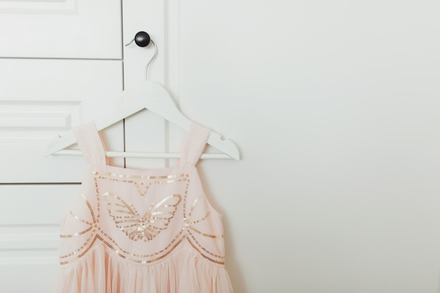 Beautiful dressy lush pink dress for girls on hanger at the background of white wardrobe.