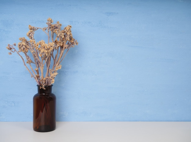 Beautiful dried flowers in glass vase set on white wood table with blue wall background with copy space, soft tone still life