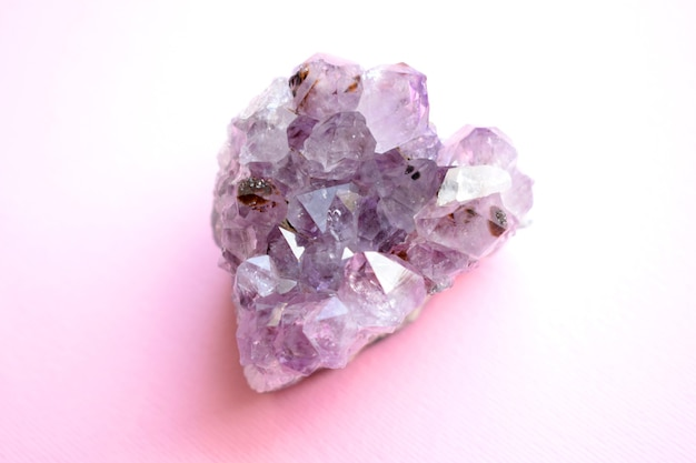 분홍색 배경에 하트 모양의 천연 보라색 광물 자수정의 아름다운 드루즈. 보석의 큰 결정체.