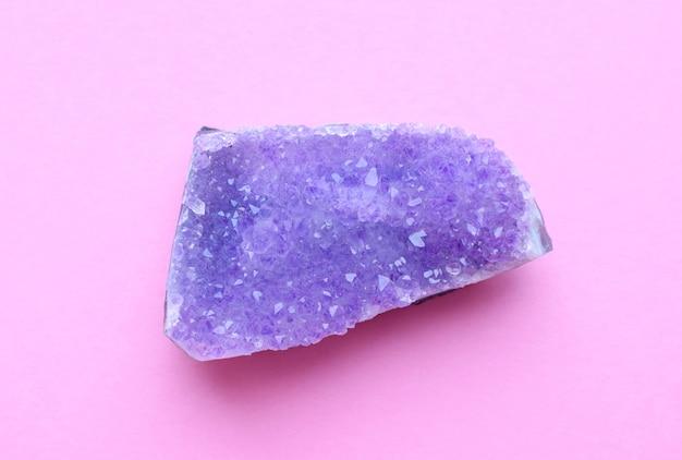 Красивая друза натурального фиолетового минерального аметиста на розовой стене. крупные кристаллы драгоценных камней.