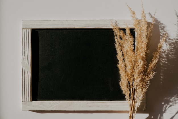 Beautiful dry reeds bouquet near black graphite board in white frame.