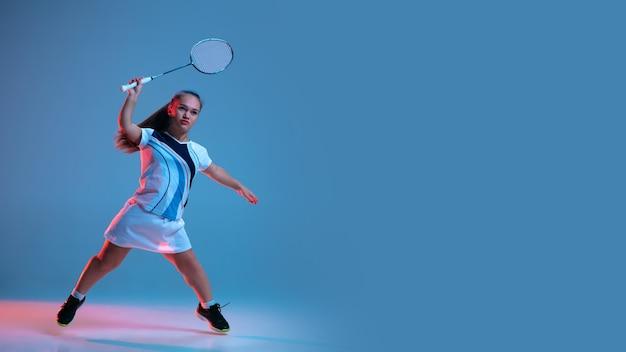 ネオンの光の青い背景に分離されたバドミントンで練習している美しい小人女性