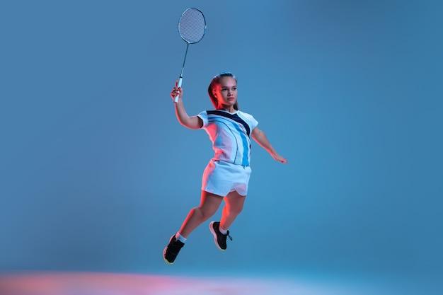 네온 불빛에 파란색으로 격리된 배드민턴에서 연습하는 아름다운 난쟁이 여자