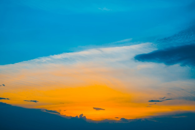 Beautiful early blue cloudy sky with orange sunlight. atmospheric cobalt of colorful sunrise with dense clouds and bright yellow sunny light for copy space. cyan heaven above clouds.