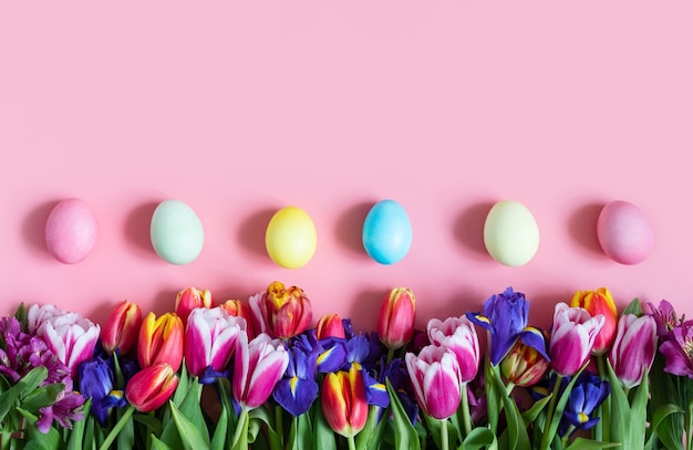 Beautiful easter border with spring flowers and eggs on a pink background. easter floral background. copy space, top view, flat lay. space for text.
