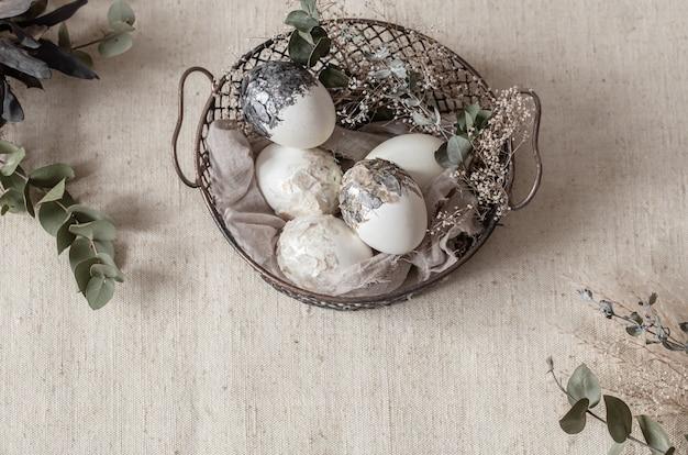 Belle uova di pasqua in un cesto decorato con fiori secchi. felice pasqua concetto.