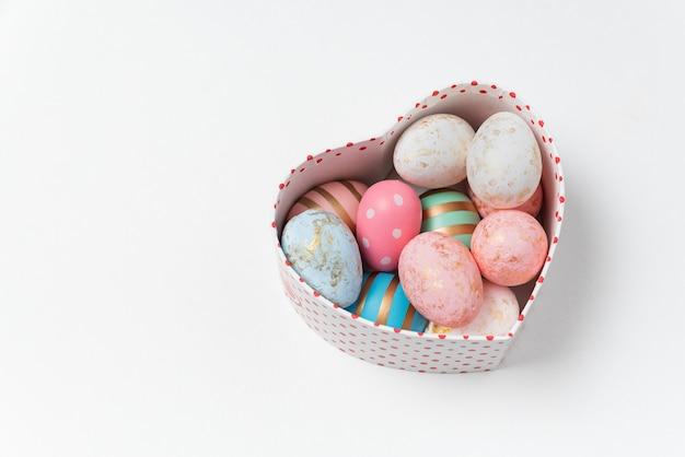 白い背景の上のハートの形のボックスで美しいイースターの卵。イースター、おめでとう