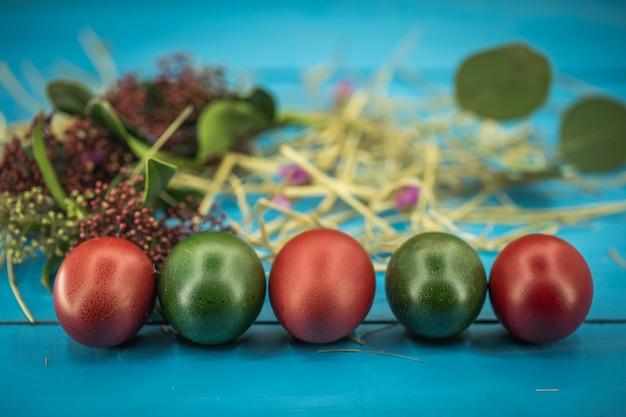 Красивые пасхальные яйца на синем дереве, концепция пасхи