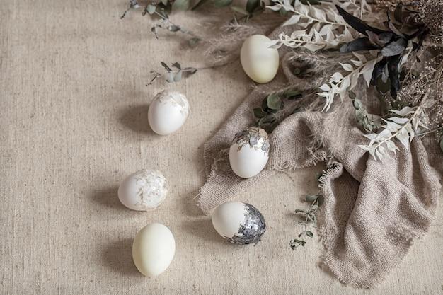 Bellissime uova di pasqua sparse sul tessuto strutturato. concetto di arredamento di pasqua.
