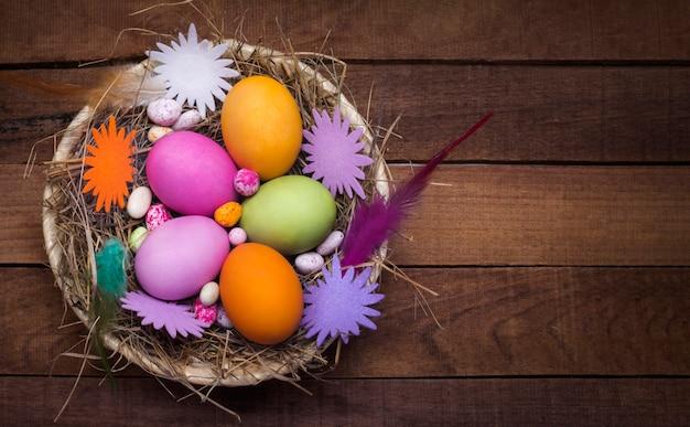 Красивые пасхальные яйца с украшениями в тарелке на деревенском столе лежат плоско.