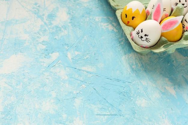아름 다운 부활절 프레임, 부활절 달걀 밝은 파란색 배경에 계란 판지에 토끼와 병아리로 그린.