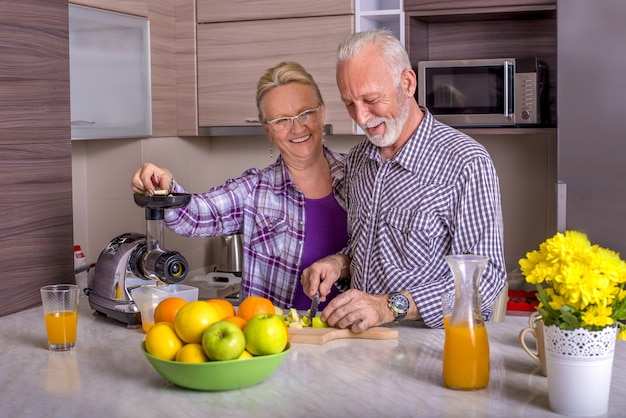 Bella coppia di anziani che cucinano in cucina con a vicenda