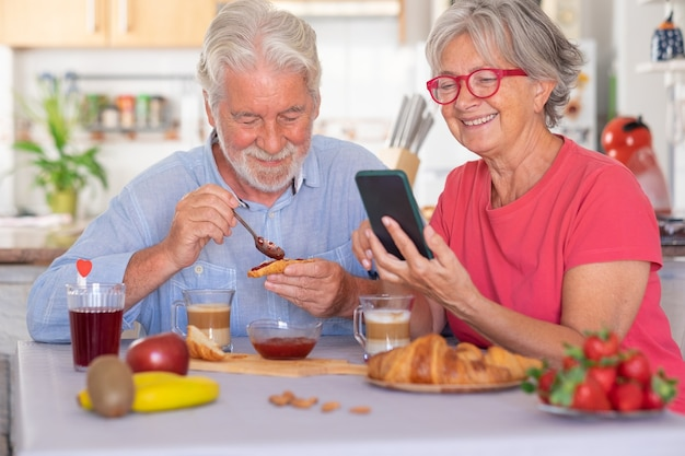 Beautiful elderly couple having breakfast at home woman using smart phone senior people relaxed