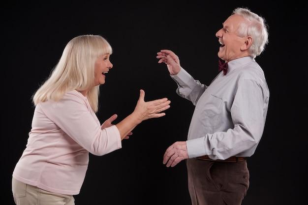 Beautiful elderly couple joking isolated on black