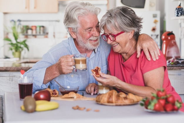 Beautiful elderly couple laughing having breakfast at home. senior people relaxed and happy