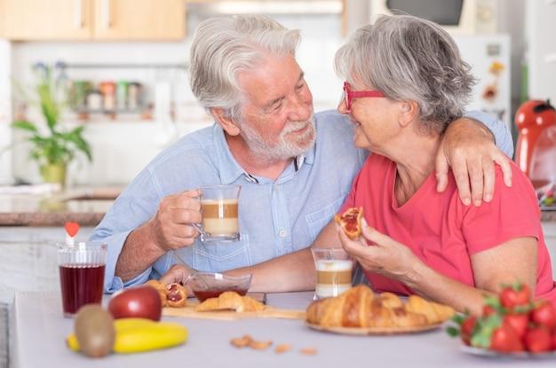 Красивая пожилая пара улыбается за завтраком дома. старшие люди расслаблены и счастливы