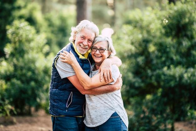 Красивая пожилая пара пожилых людей обнимаются и остаются в любви, трогательно во время отдыха на свежем воздухе в лесном лесу