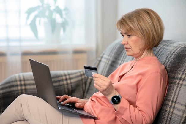 Красивая пожилая старшая женщина сидит на диване у себя дома с портативным компьютером, покупая, используя, держа