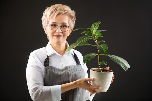 Красивая пожилая женщина в фартуке и очках с растением