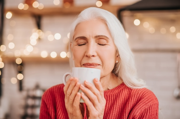 彼女のお茶の匂いを嗅ぐ赤いブラウスの美しい年配の女性