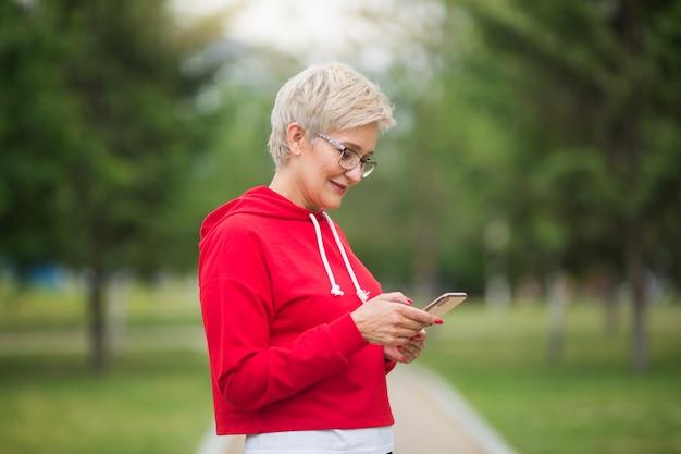公園で彼女の手に電話を持つスポーツウェアの美しい年配の女性