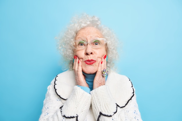 Beautiful elderly woman keeps hands on face folds red painted lips wears spectacles white jumper has well cared complexion