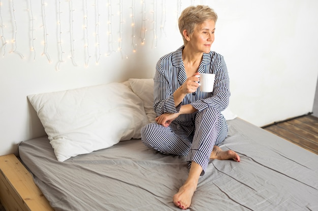 Beautiful elderly woman in pajamas in bed