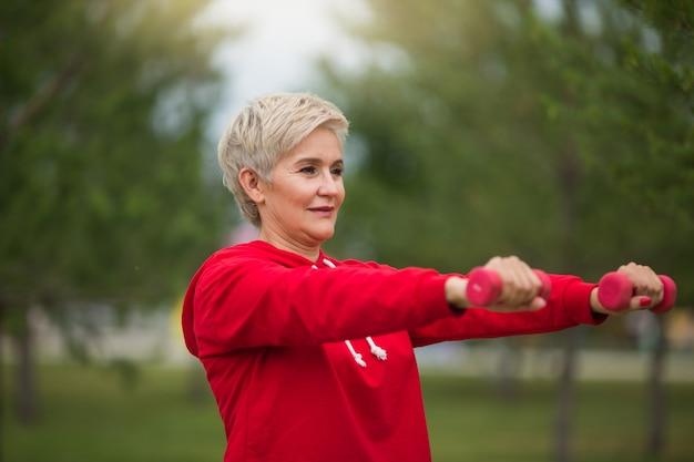 짧은 머리를 가진 아름다운 노인 여성이 공원에서 스포츠에 들어갑니다.