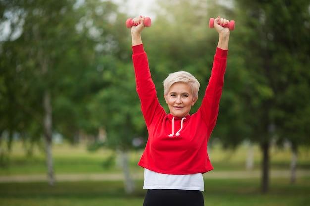 Красивая пожилая женщина с короткой стрижкой занимается спортом в парке